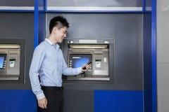 Χαμογελώντας νέος επιχειρηματίας που στέκεται μπροστά από το ATM και που εξετάζει το τηλέφωνό του Στοκ Εικόνες