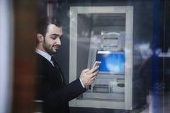 Χαμογελώντας νέος επιχειρηματίας που στέκεται μπροστά από το ATM και που εξετάζει το τηλέφωνό του Στοκ Φωτογραφίες