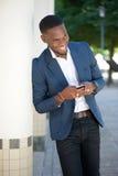 Χαμογελώντας νέος επιχειρηματίας που στέλνει το μήνυμα κειμένου από το κινητό τηλέφωνο Στοκ εικόνα με δικαίωμα ελεύθερης χρήσης