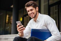 Χαμογελώντας νέος επιχειρηματίας που χρησιμοποιεί το τηλέφωνο κυττάρων υπαίθρια Στοκ Εικόνες