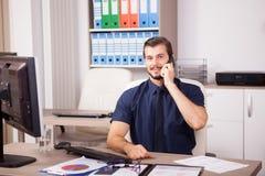 Χαμογελώντας νέος επιχειρηματίας στο μπλε πουκάμισο και δεσμός που μιλά στο π Στοκ φωτογραφίες με δικαίωμα ελεύθερης χρήσης