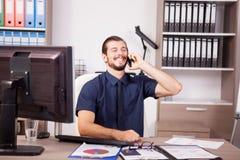 Χαμογελώντας νέος επιχειρηματίας στο μπλε πουκάμισο και δεσμός που μιλά στο π Στοκ Εικόνα