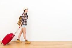 Χαμογελώντας νέος θηλυκός ταξιδιώτης που τραβά την κόκκινη βαλίτσα Στοκ εικόνες με δικαίωμα ελεύθερης χρήσης