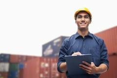Χαμογελώντας νέος μηχανικός στην προστατευτική ένδυση εργασίας σε ένα στέλνοντας ναυπηγείο που εξετάζει το φορτίο Στοκ φωτογραφίες με δικαίωμα ελεύθερης χρήσης