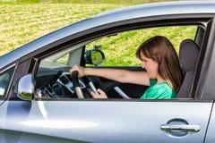 Χαμογελώντας νέος οδηγός γυναικών που διαβάζει/που δακτυλογραφεί ένα μήνυμα κειμένου Στοκ φωτογραφία με δικαίωμα ελεύθερης χρήσης