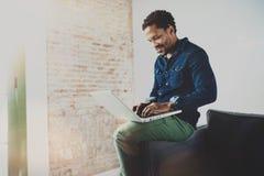 Χαμογελώντας νέο αφρικανικό άτομο που εργάζεται με το lap-top καθμένος στον καναπέ στη σύγχρονη coworking θέση του Έννοια ευτυχού Στοκ εικόνες με δικαίωμα ελεύθερης χρήσης