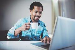 Χαμογελώντας νέο αφρικανικό άτομο που κάνει την τηλεοπτική συνομιλία μέσω του lap-top με τους συνεργάτες πίνοντας το άσπρο μαύρο  Στοκ Εικόνα