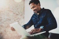 Χαμογελώντας νέο αφρικανικό άτομο που χρησιμοποιεί το lap-top καθμένος στη σύγχρονη coworking θέση του Έννοια των ευτυχών επιχειρ Στοκ φωτογραφία με δικαίωμα ελεύθερης χρήσης
