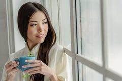 Χαμογελώντας νέο γυναικείο δοκιμάζοντας τσάι Στοκ εικόνες με δικαίωμα ελεύθερης χρήσης