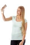 Χαμογελώντας νέο κορίτσι που καθιστά selfie τη φωτογραφία απομονωμένη σε ένα λευκό Στοκ εικόνες με δικαίωμα ελεύθερης χρήσης