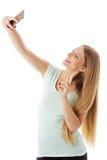 Χαμογελώντας νέο κορίτσι που καθιστά selfie τη φωτογραφία απομονωμένη σε ένα λευκό Στοκ φωτογραφία με δικαίωμα ελεύθερης χρήσης