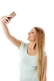Χαμογελώντας νέο κορίτσι που καθιστά selfie τη φωτογραφία απομονωμένη σε ένα λευκό Στοκ Φωτογραφίες