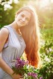 Χαμογελώντας νέο κορίτσι που κρατά μια δέσμη των λουλουδιών lupine στον ηλιόλουστο θερινό τομέα Στοκ Εικόνες