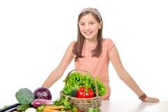 Χαμογελώντας νέο κορίτσι που στέκεται πίσω από τα λαχανικά σωρών Στοκ εικόνα με δικαίωμα ελεύθερης χρήσης