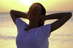 Χαμογελώντας νέο κορίτσι στην παραλία στο ηλιοβασίλεμα στοκ εικόνες
