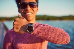 Χαμογελώντας νέο μαύρο αγόρι που φορά το καθιερώνον τη μόδα έξυπνο ρολόι Στοκ Εικόνες