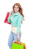 Χαμογελώντας νέο redhead κορίτσι με τα ζωηρόχρωμα shoppingbags στοκ φωτογραφίες με δικαίωμα ελεύθερης χρήσης