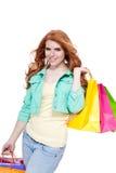 Χαμογελώντας νέο redhead κορίτσι με τα ζωηρόχρωμα shoppingbags στοκ εικόνες