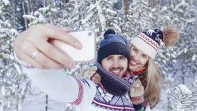 Χαμογελώντας νεαρός άνδρας και ευτυχής νέα γυναίκα που παίρνουν τη φωτογραφία τους στο όμορφο χειμερινό δάσος απόθεμα βίντεο