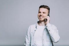 Χαμογελώντας νεαρός άνδρας με τη γενειάδα σε ένα άσπρο πουκάμισο στοκ φωτογραφία