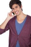 Χαμογελώντας νεαρός άνδρας με το κινητό τηλέφωνο Στοκ φωτογραφία με δικαίωμα ελεύθερης χρήσης