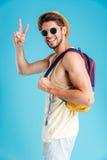 Χαμογελώντας νεαρός άνδρας με το σακίδιο πλάτης που παρουσιάζει σημάδι ειρήνης Στοκ φωτογραφία με δικαίωμα ελεύθερης χρήσης