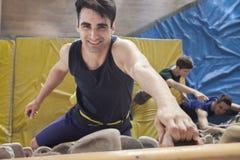 Χαμογελώντας νεαρός άνδρας που αναρριχείται επάνω σε έναν τοίχο αναρρίχησης σε μια εσωτερική γυμναστική αναρρίχησης, άμεσα ανωτέρω στοκ φωτογραφίες