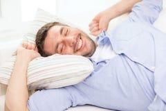 Χαμογελώντας νεαρός άνδρας που βρίσκεται στον καναπέ στο σπίτι Στοκ φωτογραφίες με δικαίωμα ελεύθερης χρήσης