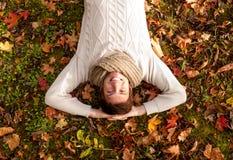 Χαμογελώντας νεαρός άνδρας που βρίσκεται στο έδαφος στο πάρκο φθινοπώρου στοκ εικόνα