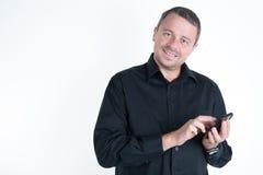 Χαμογελώντας νεαρός άνδρας που εξετάζει το έξυπνο τηλέφωνό του Στοκ Φωτογραφίες