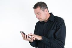 Χαμογελώντας νεαρός άνδρας που εξετάζει το έξυπνο τηλέφωνό του Στοκ φωτογραφία με δικαίωμα ελεύθερης χρήσης