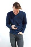 Χαμογελώντας νεαρός άνδρας που εξετάζει το κινητό τηλέφωνο Στοκ εικόνα με δικαίωμα ελεύθερης χρήσης