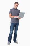 Χαμογελώντας νεαρός άνδρας που εργάζεται στο lap-top του Στοκ φωτογραφίες με δικαίωμα ελεύθερης χρήσης