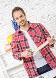 Χαμογελώντας νεαρός άνδρας που μετρά τον ξύλινο πίνακα Στοκ φωτογραφίες με δικαίωμα ελεύθερης χρήσης