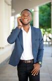 Χαμογελώντας νεαρός άνδρας που περπατά και που μιλά με κινητό τηλέφωνο Στοκ εικόνες με δικαίωμα ελεύθερης χρήσης