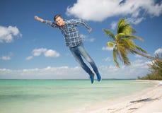 Χαμογελώντας νεαρός άνδρας που πετά στον αέρα Στοκ Εικόνες