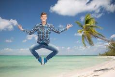 Χαμογελώντας νεαρός άνδρας που πηδά στον αέρα Στοκ φωτογραφία με δικαίωμα ελεύθερης χρήσης