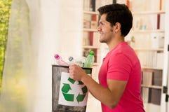Χαμογελώντας νεαρός άνδρας που φέρνει ένα μικρό μαύρο σύνολο συλλεκτών απορριμάτων του πλαστικού, ανακύκλωσης και του χρηματοκιβω Στοκ φωτογραφίες με δικαίωμα ελεύθερης χρήσης
