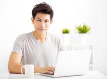 Χαμογελώντας νεαρός άνδρας που χρησιμοποιεί το lap-top Στοκ Εικόνα