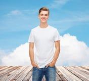 Χαμογελώντας νεαρός άνδρας στην κενή άσπρη μπλούζα Στοκ εικόνα με δικαίωμα ελεύθερης χρήσης