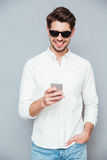 Χαμογελώντας νεαρός άνδρας στο άσπρο πουκάμισο και γυαλιά ηλίου που χρησιμοποιούν το smartphone Στοκ φωτογραφία με δικαίωμα ελεύθερης χρήσης