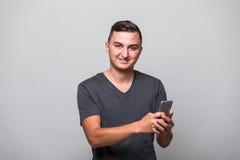 Χαμογελώντας νεαρός άνδρας στο άσπρο πουκάμισο που χρησιμοποιεί το smartphone Στοκ φωτογραφίες με δικαίωμα ελεύθερης χρήσης