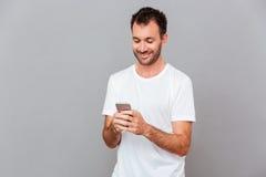 Χαμογελώντας νεαρός άνδρας στο άσπρο πουκάμισο που χρησιμοποιεί το smartphone Στοκ εικόνα με δικαίωμα ελεύθερης χρήσης