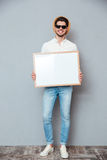 Χαμογελώντας νεαρός άνδρας στο καπέλο και γυαλιά ηλίου που κρατούν το λευκό πίνακα Στοκ Φωτογραφία
