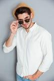 Χαμογελώντας νεαρός άνδρας στο καπέλο που στέκεται και που κοιτάζει πέρα από τα γυαλιά ηλίου Στοκ φωτογραφίες με δικαίωμα ελεύθερης χρήσης