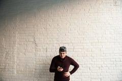 Χαμογελώντας νεαρός άνδρας στο καπέλο του μπέιζμπολ και πουλόβερ με το κινητό τηλέφωνο στα χέρια Στοκ Φωτογραφία