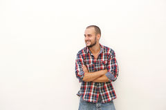 Χαμογελώντας νεαρός άνδρας στο πουκάμισο καρό που στέκεται με τα όπλα που διασχίζονται Στοκ Φωτογραφίες