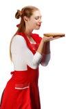 Χαμογελώντας νοικοκυρά στην κόκκινη ποδιά με τα αστεία ponytails και το ξύλινο γ Στοκ Εικόνες