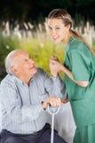 Χαμογελώντας νοσοκόμα που βοηθά το ανώτερο άτομο για να σηκωθεί από Στοκ Εικόνα