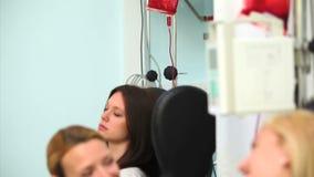 Χαμογελώντας νοσοκόμα που εξετάζει έναν θηλυκό ασθενή απόθεμα βίντεο